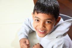 Junger glücklicher ethnischer Schulejunge 9, der in der Kategorie sitzt Stockfotografie