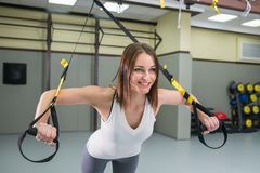 Junger glücklicher Frauenbodybuilder an der Turnhalle, die elastisches Seil tut, trainiert mit mit trx Eignungsbügeln stockfotografie