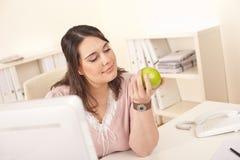 Junger glücklicher Geschäftsfrauholdingapfel im Büro lizenzfreies stockfoto