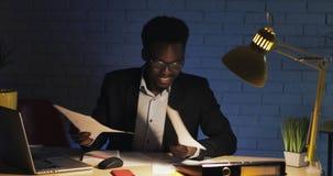 Junger glücklicher Geschäftsmann, der Dokumente am Schreibtisch im Nachtbüro liest Mann, der an den Dokumenten arbeitet stock footage