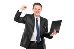 Junger glücklicher Geschäftsmann, der einen Laptop anhält Stockfotos