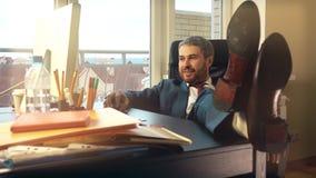 Junger glücklicher Geschäftsmann, der an seinem Arbeitsplatz sich entspannt und seine Füße auf den Schreibtisch setzt Video 4K stock video