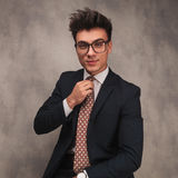 Junger glücklicher Geschäftsmann, der seins Bindung regelt Lizenzfreies Stockfoto
