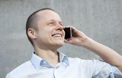 Junger glücklicher Geschäftsmann, der am Telefon spricht. Stockbild