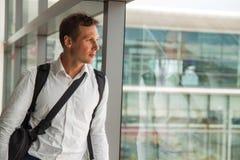 Junger glücklicher Geschäftsmann im weißen Hemd, das auf seinen Flug wartet lizenzfreies stockfoto
