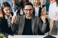 Junger glücklicher Geschäftsmann mit wirklich eindrucksvollen Leistungen, Siegtanz, die schnell wachsende Firma, vergütet, gewann lizenzfreie stockfotos