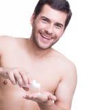 Junger glücklicher gutaussehender Mann gießt Lotion. Stockfotografie