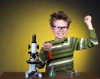 Junger glücklicher Junge, der Experimente durchführt. Wenig sci Stockbild