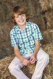 Junger glücklicher Jungen-sitzendes Lächeln auf Hay Bales Stockfoto