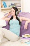 Junger glücklicher Kursteilnehmer entspannen sich hören Musik Lizenzfreie Stockfotografie