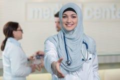 Junger glücklicher lächelnder weiblicher moslemischer Doktor, der Hand für Händeschütteln gibt lizenzfreies stockfoto