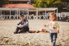 Junger glücklicher liebevoller Vater mit der kleinen Tochter, die Zeit am Strand genießt, Vater kümmert sich um Tochter, glücklic lizenzfreie stockfotografie