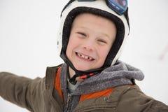 Junger glücklicher, lustiger Junge lacht im Sturzhelm, weißer Hintergrund Stockbilder