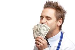 Junger glücklicher männlicher Doktor, der Dollarrechnungen küßt Stockfoto