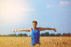 Junger glücklicher Mann auf einem Weizengebiet Lizenzfreie Stockfotos