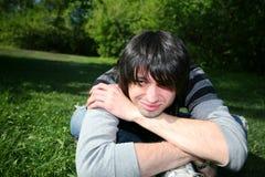 Junger glücklicher Mann, der auf dem Gras und dem Lächeln sitzt. Lizenzfreies Stockfoto