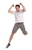 Junger glücklicher Mann, der auf einen weißen Hintergrund springt lizenzfreies stockfoto