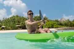 Junger glücklicher Mann, der auf einer Tropeninsel in den Malediven Kayak fährt Freies blaues Wasser stockbilder