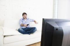 Junger glücklicher Mann, der fernsieht, das Wohnzimmersofa zu Hause zu sitzen schaut entspannt, Fernsehen genießend Lizenzfreies Stockbild