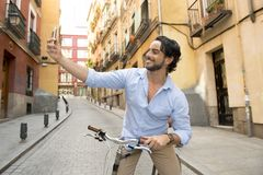 Junger glücklicher Mann, der selfie mit Handy auf Retro- kühlem Weinlesefahrrad nimmt lizenzfreie stockbilder