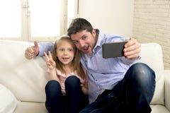 Junger glücklicher Mann, der Spaß mit seiner kleinen netten blonden Tochter macht selfie Foto mit Handy hat Lizenzfreies Stockfoto