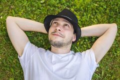 Junger glücklicher Mann ist, entspannend liegend und im Gras im Park und im Denken oder im Träumen Stockfotos