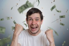 Junger glücklicher Mann ist Sieger der Lotterie Geld fallen von der Spitze lizenzfreies stockbild
