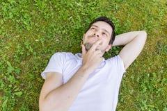 Junger glücklicher Mann liegt auf grünem Gras und dem Denken oder dem Träumen Stockfotos