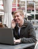 Junger glücklicher Mann mit Telefon und Laptop Lizenzfreie Stockbilder
