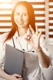Junger glücklicher netter Doktor in der weißen Uniform o.k. gestikulierend stockfoto