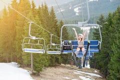 Junger glücklicher Skifahrer ist steigende Hand oben auf Skiaufzug und dem Reiten bis zur Spitze des Berges mit Skiausrüstun Lizenzfreies Stockbild
