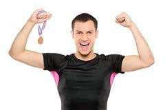 Junger glücklicher Sportler, der eine Goldmedaille anhält Stockfotografie
