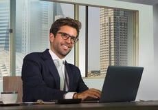 Junger glücklicher und attraktiver erfolgreicher Geschäftsmann, der im modernen Büro im zentralen Geschäftsgebietlächeln zufriede stockfotografie