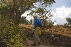Junger glücklicher und attraktiver sportlicher Wanderermann mit dem Trekkingsrucksack, der an der freien genießenden Reiseflucht  stockfotografie