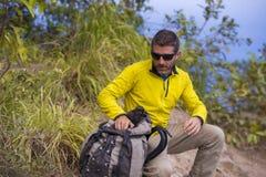 Junger glücklicher und attraktiver sportlicher Wanderermann mit dem Trekkingsrucksack, der an der freien genießenden Reiseflucht  lizenzfreie stockfotografie