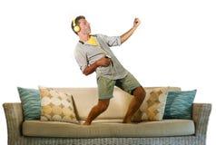 Junger glücklicher und aufgeregter Mann, der auf die Sofacouch hört Musik mit dem Handy und Kopfhörern spielen Luftgitarre verrüc lizenzfreies stockfoto