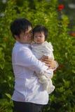 Junger glücklicher und stolzer Mann als Vater des süßen kleinen Babys, das ihre Tochter vor Blumengarten am Feiertagserholungsort lizenzfreie stockfotografie