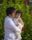 Junger glücklicher und stolzer Mann als Vater des süßen kleinen Babys, das ihre Tochter vor Blumengarten am Feiertagserholungsort stockfotos