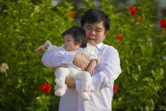 Junger glücklicher und stolzer Mann als Vater des süßen kleinen Babys, das ihre Tochter vor Blumengarten am Feiertagserholungsort stockfoto