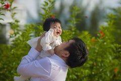 Junger glücklicher und stolzer Mann als Vater des süßen kleinen Babys, das ihre Tochter vor Blumengarten am Feiertagserholungsort lizenzfreie stockbilder