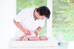 Junger glücklicher Vater, der mit seinem neugeborenen Babysohn spielt Lizenzfreie Stockbilder