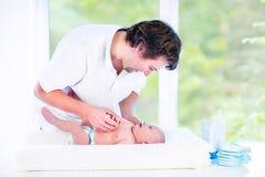 Junger glücklicher Vater, der mit seinem neugeborenen Babysohn spielt Lizenzfreie Stockfotos
