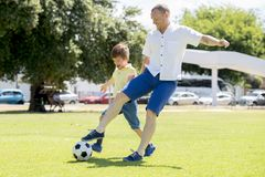 Junger glücklicher Vater und wenig aufgeregt 7 oder 8 Jahre alte Sohn, die zusammen Fußballfußball auf dem Stadtparkgarten läuft  Lizenzfreie Stockbilder