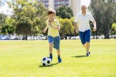 Junger glücklicher Vater und wenig aufgeregt 7 oder 8 Jahre alte Sohn, die zusammen Fußballfußball auf dem Stadtparkgarten läuft  Stockbild