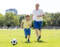 Junger glücklicher Vater und wenig aufgeregt 7 oder 8 Jahre alte Sohn, die zusammen Fußballfußball auf dem Stadtparkgarten läuft  Stockfoto