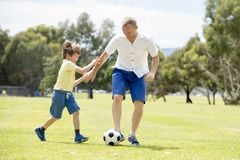 Junger glücklicher Vater und wenig aufgeregt 7 oder 8 Jahre alte Sohn, die zusammen Fußballfußball auf dem Stadtparkgarten läuft  Stockfotos