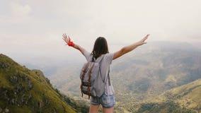 Junger glücklicher weiblicher Blogger Reise der hinteren Ansicht mit Rucksackständen mit den Armen weit offen am epischen Bergbli stock footage