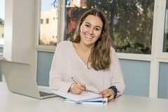 Junger glücklicher weiblicher Jugendlichhochschulstudent, der in der Schule mit dem Klassenzimmer des Computerlaptops lächelt auf Lizenzfreies Stockfoto