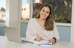 Junger glücklicher weiblicher Jugendlichhochschulstudent, der in der Schule mit dem Klassenzimmer des Computerlaptops lächelt auf Lizenzfreie Stockbilder