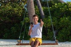 Junger gl?cklicher Mann gesetzt auf einem Schwingen und der Anwendung seines Telefons Wei?er Sand und Dschungel als Hintergrund lizenzfreie stockfotos